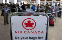 263806-air-canada-travellers-wait-at-the-check-in-area-as-baggage-handlers-at